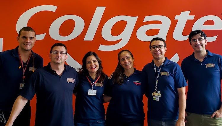 Group of 6 people smiling, all wearing navy blue shirts, in front of a large Colgate banner