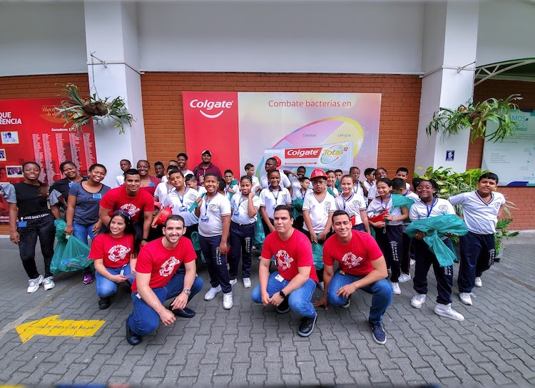 Diverse group of people, including children and adults, posing in front of a Colgate banner, on a brick road