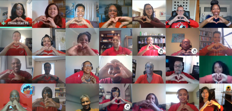 28 people creating a heart-shape with their hands